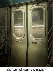 New York City Subway doors, closed while train is moving, with light-streaks visible through the windows