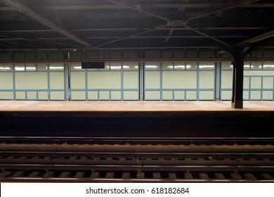 New York City subway platform late a night.  Green glass walls at subway station in Brooklyn, New York. Subway tracks, nobody on the subway platform.