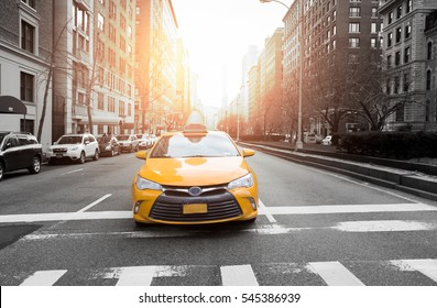 New York City taxi in yellow color in the traffic light with building and car in background