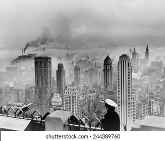 New York City under smog when weather conditions prevented smoke from dispersing. View from the Empire State Building includes the Lincoln Building and RCA Building. 1949 photo by Edward Ratcliffe.