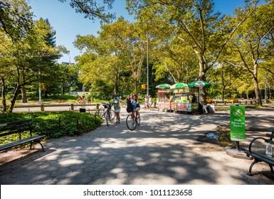 New York City, United States - August 24, 2017: In Central Park, kiosk of a hot dog and ice cream sidewalk vendor, with people walking and women with bicycle.