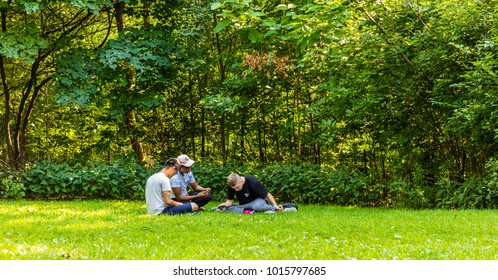 New York City, United States - August 24, 2017: Three guys are playing a role-playing game in Central Park.