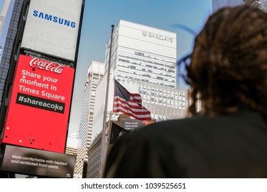 New York City, United States - February 18, 2018: View of several advertisements and buildings towering above unassuming, out of focus person at Times Square.
