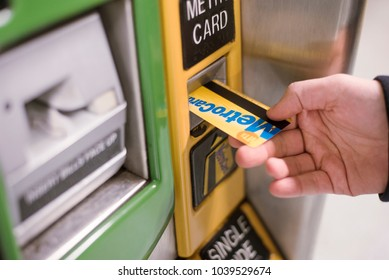 New York City, United States - February 18, 2018: Inserting the MetroCard into payment machine to buy credits to use New York's subway system.