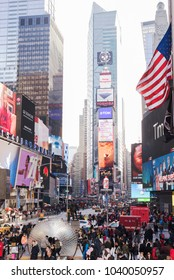New York City, United States - February 18, 2018: View of Times Square during busy day, with crowds of people enjoying scenes as the American flag  flutters or waves in wind above.