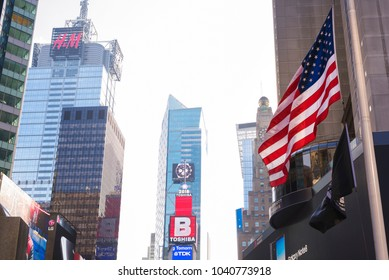 New York City, United States - February 18, 2018: Alternate view of New York's Times Square showing top of buildings and some advertisements, with American flag fluttering or waving in foreground.