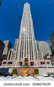 New York City, United States - August 25, 2008: Rockefeller Center with 30 Rockefeller Plaza building, statue of Prometheus, Lower Plaza with umbrellas, and stalls of the Farmers Market in the backg