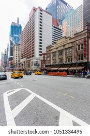 New York City, United States - August 25, 2017: Near the corner of 7th Avenue and West 52nd street, Midtown Manhattan, with white stripes on the asphalt in foreground.