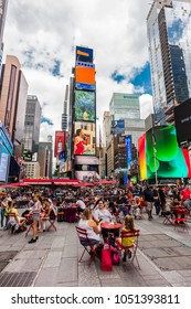 New York City, United States - August 25, 2017: Times Square (Midtown Manhattan), with people, and customers sitting at the tables of an outdoor bar.