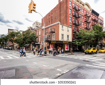 New York City, United States - August 25, 2017: Corner of Bkeecker Street and Christopher Street, West Village (Greenwich Village, Manhattan), with people, cars, and shops.