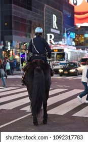 New York City, New York, United States  - February 20, 2018: Police officer on horse patrolling streets of Times Square at night, with tourists and commuters seen in background. Seen from behind.
