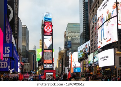 New York City, United States - November 17 2018:   Tourists, shoppers and locals throng amnogst the neon signs and billboards of Times Square