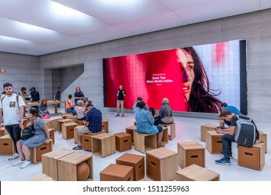 New York City, United States of America - September 20th 2019: Visiting the reopened Apple Store in 5th Avenue after the release of the new iPhone 11, viewing the education corner with people waiting.