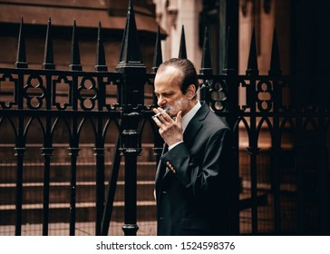 New York City, New York / United States - August 10, 2019: Businessman has a smoke break in downtown Manhattan in a beautiful suit.