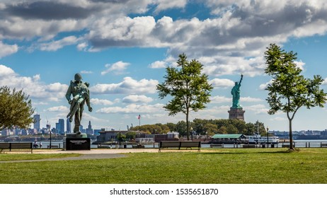 New York City, United States of America - 24rd September 2019: Visiting the Liberty State Park in New Jersey. Viewing a memorial statue of a war with the Statue of Liberty and the skyline of Manhattan