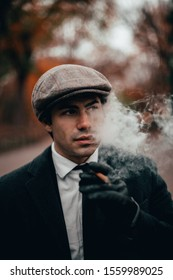 New York City, New York / United States - November 13, 2019: Vintage style man in suit, hat, and cigar, poses in Central Park on a chilly fall day.