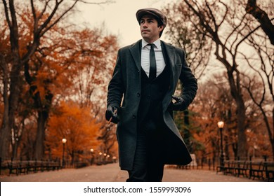 New York City, New York / United States - November 13, 2019: Vintage clothed model walks down a quite fall path in Central Park while smoking a cigar.