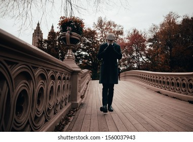 New York City, New York/ United States - November 13, 2019: Man in vintage clothing smokes a cigar in the park during a chilly fall day. The classic style is similar to the Peaky Blinder clothing.