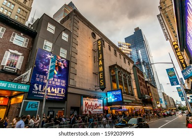 New York City, United States of America - 1^4th September 2019: A photographer visiting NYC, taking pictures of the Times Square at night with crowds of tourists walking through the streets.