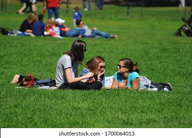 New York City, United States of America – September 14, 2014. Three female New Yorkers lounging at Sheep Meadow in Central Park on a sunny day.