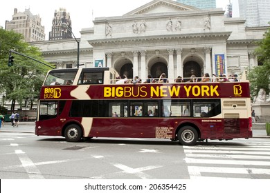 New York City, New York, United States - July 10, 2014:Tourist riding a double-decker tour bus in front of the New York City Library on July 10, 2014
