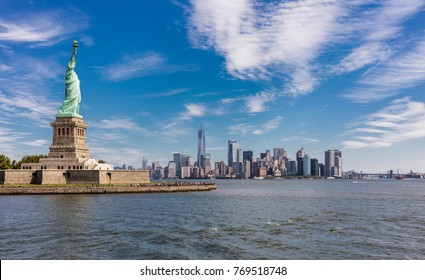New York City, United States - August 23, 2017: Liberty Island with the Liberty Statue surrouded by visitors, under a cloudy sky, and the skyline of Manhattan in the background.