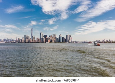 New York City, United States - August 23, 2017: Skyline of Manhattan from Liberty Island, under a cloudy sky, and a boat on the sea.