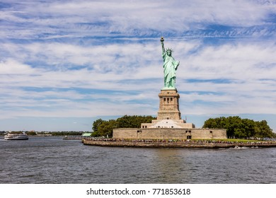 New York City, United States - August 23, 2017: Liberty Island with the Liberty Statue surrounded by visitors, under a cloudy sky, an a ferry on the sea.