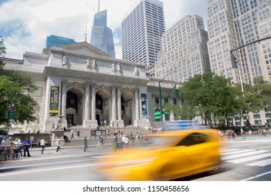 New York City, USA - 08/31/2017 : Yellow taxi passing by main entrance of the New York Public Library