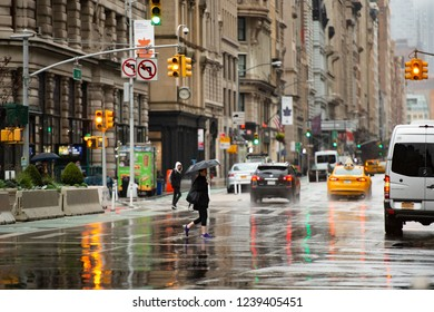 NEW YORK CITY - USA - 29 OCTOBER 2017. Tourists and cars in Times Square during a rainy day. Times Square is a major commercial intersection, tourist destination in Manhattan.