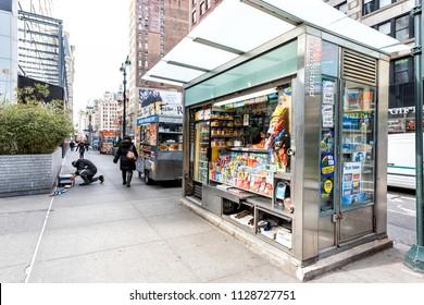 New York City, USA - April 7, 2018: Midtown Manhattan with street sidewalk on Broadway, Newsstand with newspaper, magazines, candy