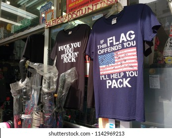 """New York City, New York / USA - April 13 2018: Souvenir t-shirts for sale at a gift shop in NYC. One shirt featuring the American flag asserts, """"If This Flag Offends You, I'll Help You Pack""""."""
