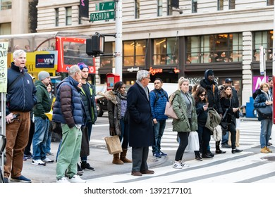 New York City, USA - April 6, 2018: Manhattan NYC buildings of midtown with 7th avenue road sign and Fashion with many people waiting at crosswalk on street crosswalk