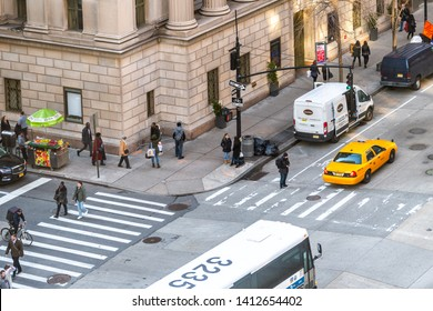 New York City, USA - April 6, 2018: Aerial high angle view of urban sixth avenue street in NYC Herald Square Midtown with pedestrians crossing road and yellow taxi cab on corner