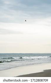 New York City, New York / USA - April 24 2020: Atlantic Ocean beach at Rockaway beach in New York. Daytime blue beach waves.