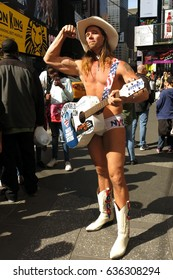 New York City, USA - April 30, 2016: The Naked Cowboy, one of New York City's most famous street performers, plays to his strengths, flexing a bicep in Times Square.
