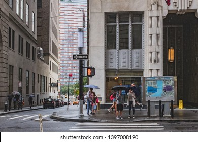 New York City, USA - Aug. 11, 2018: Pedestrians waiting on sidewalk to cross the street in a raining day in lower Manhattan
