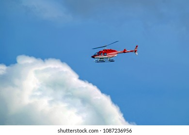 New York City, USA - August 11, 2012: Red with white Bell 407 helicopter in flight