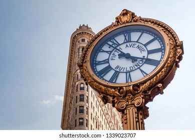New York City, New York, USA - August 20th 2017 The historical 1909 cast iron street clock at 200 Fifth Avenue with the famous icon Flatiron building in the background.