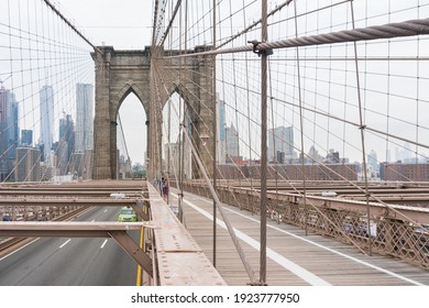 New York City, USA - August 6, 2019:People walk across the famous Brooklyn Bridge during a cloudy day.
