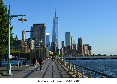 New York City, USA - August 9, 2015: Runners and walkers enjoying a summer day on the Hudson River Esplanade with World Trade Center Tower One in the background in New York City.