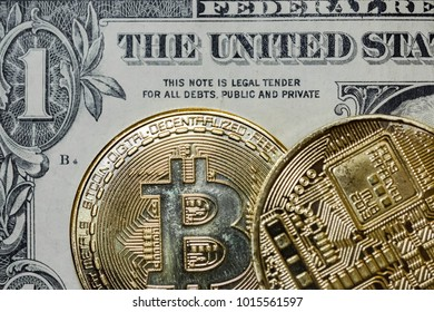 New York City, New York, USA - Circa January 2018: Close-up image of a pair of Bitcoins seen on top of a regular One Dollar Bill. Detail of the Bitcoin coinage is clearly visible, as is the colouring.