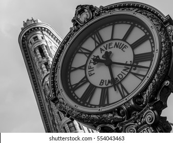 NEW YORK CITY, USA - CIRCA SEPTEMBER, 2015: The Fifth Avenue Building Clock with the Flatiron Building in the background. Located midtown Manhattan on fifth avenue, NYC.