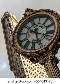 NEW YORK CITY, USA - CIRCA SEPTEMBER, 2015: The Fifth Avenue Building Clock with the sun hitting the Flatiron Building in the background. Located midtown Manhattan on fifth avenue, NYC.