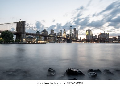 NEW YORK CITY, USA - CIRCA JUNE, 2016: A view of the Manhattan skyline before the sun starts to set. The East River looks smooth and misty by the use of a long exposure camera setting.