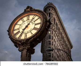 NEW YORK CITY, USA - CIRCA SEPTEMBER, 2015: The Fifth Avenue Building Clock at sunset with the Flatiron Building in the background. Located midtown Manhattan on fifth avenue, NYC.