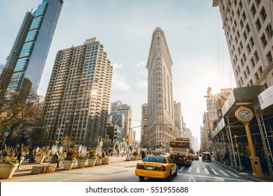 New York City, USA - Dec 1, 2016: Flat Iron building facade, one of the first skyscrapers ever built, with NYC Fifth Avenue and taxi cabs
