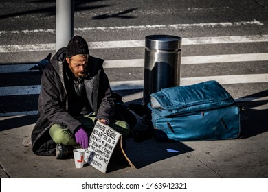 """New York City, New York / USA - December 19, 2018: Homeless veteran asking for $35 bus fare to visit his brother in Delaware. """"I fought for this county! please fight for me"""" written a cardboard sign."""