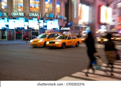 New York City, New York / USA - Feb 15, 2012: NYC Taxis at night time cruise out of Times Square on Broadway.  Taxis are an important form of transportation on the congested streets of Manhattan.