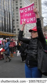 "New York City, New York / USA - January 20 2018: A female Trump supporter holds a pink sign that says, ""Women for Trump"" at the Women's March in New York City."